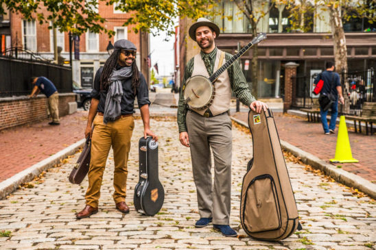 Musicians Ben Hunter and Joe Seamons on a cobblestone street with instrument cases in hand.